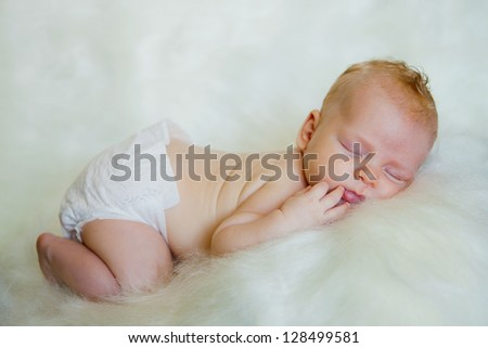 A newborn baby sleeping on a soft white background. Childhood or parenting concept.