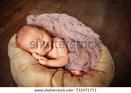 A newborn baby sleeps in a basket on a wooden floor. Beige background. A tender smile of the baby.