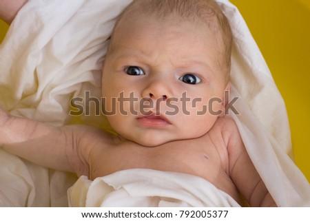 A newborn in a film is bathed in a yellow bathtub. Flat Lay. Close ...