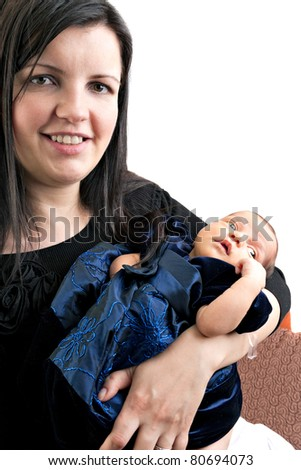 A newborn infant being held in the arms of her smiling mother isolated over a white background.