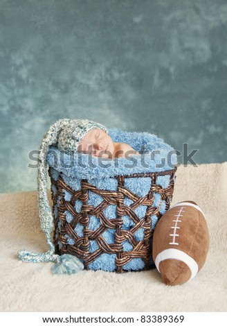 A newborn premature baby boy sleeping in a basket wearing a hat and football, lots of copy space - stock photo