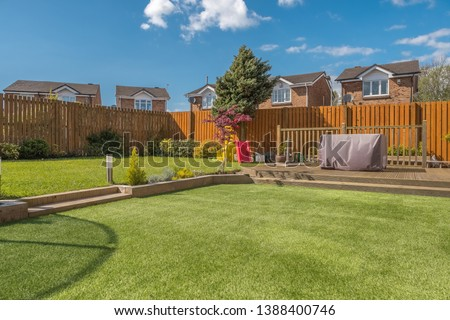 A newly completed and replanted landscaped garden with mixure of artificial and natural sown grass, borders planted, a new decking patio and garden ornaments surrounded by new erected wooden fencing.  Stock photo ©