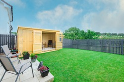 A newly completed and replanted landscaped garden with natural sown turf, a new slab patio and surrounded by new erected wooden fencing  all to a modern design and painted blue and new summer house.
