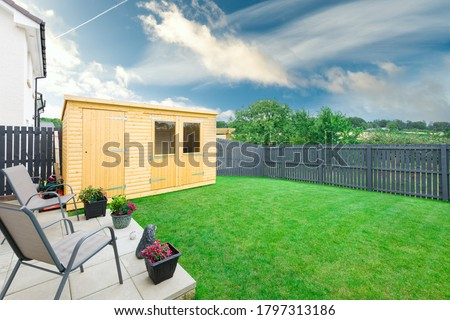 A newly completed and replanted landscaped garden with natural sown turf, a new slab patio and surrounded by new erected wooden fencing  all to a modern design and painted blue and new summer house. Сток-фото ©