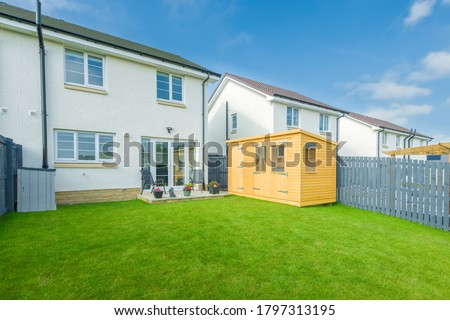 A newly completed and replanted landscaped garden with natural sown turf, a new slab patio and surrounded by new erected wooden fencing  all to a modern design and painted blue and new summer house. Stock photo ©