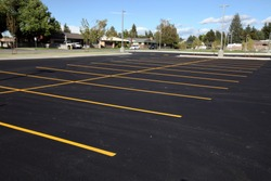 A newly completed parking lot with freshly painted yellow lines to mark the stalls.