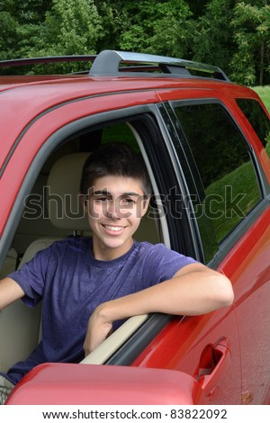 A newly licensed teenage male driver sits in his shiny new red car. Close up in vertical format showing the young caucasian man smiling as he sits behind the wheel.