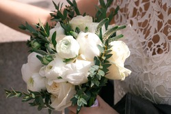 A newly wed bride holding a small bouquet of white ranunculus flowers