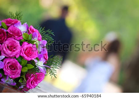 A newly wed couple walking away from a beautiful vibrant bridal bouquet