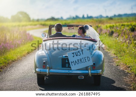 A newlywed couple is driving a convertible retro car on a country road for their honeymoon, rear view Stockfoto ©