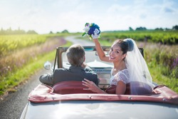 A newlywed couple is driving a retro car, the bride looks at the camera and throws her bouquet, rear view