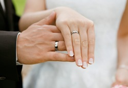 a newlyweds keep their hands together with the new wedding rings