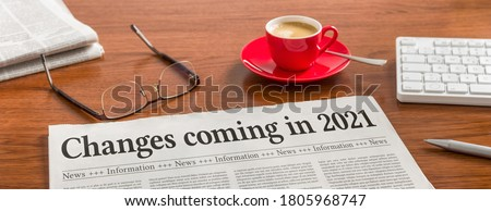 A newspaper on a wooden desk - Changes coming in 2021 Photo stock ©