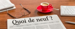 A newspaper on a wooden desk - Whats new in french - Quoi de neuf