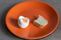 a nibbled piece of white bread and a nibbled boiled egg on an orange plate