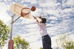 A nice and cool Afro american players playing basketball outdoors
