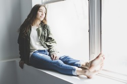 A nice and cool Teenager girl sitting on window