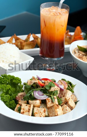 A nice assortment of Thai food and appetizers presented beautifully with fancy garnish with copy space.