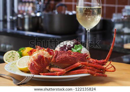 A nice, big plate filled with lobster, rice and a glass of white wine.