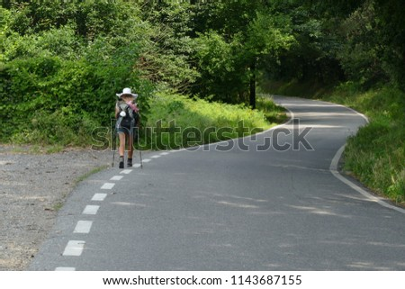 A nice blond, long-haired girl (fourteen-year-old) in the forest on the Pilgrim-Way of St. James (Camino de Santiago de Compostela) in Northern Portugal #1143687155