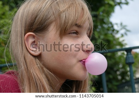 A nice blond, long-haired girl (fourteen-year-old), who amused at herself, tries to make the world's largest bubble with a bubble gum #1143705014
