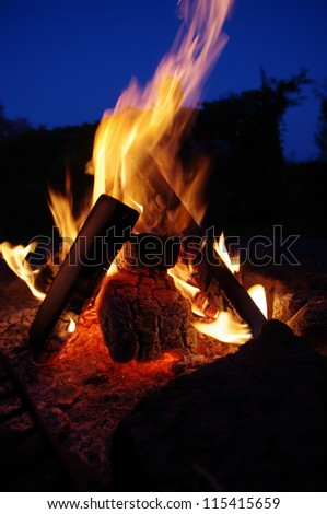 a nice campfire burning outside in summer - stock photo