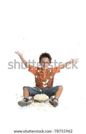 A nice caucasian and Brazilian kid playing with his popcorn, wearing a nice orange t shirt, short jeans and tennis on white background. - stock photo