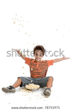 A nice caucasian and Brazilian kid playing with his popcorn, wearing a nice orange t shirt, short jeans and tennis on white background.