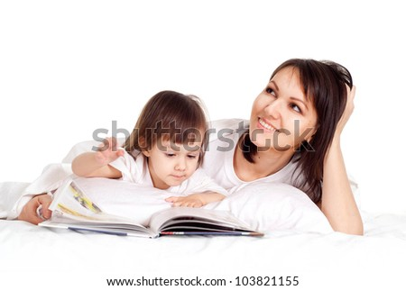 A nice Caucasian mama with her daughter lying on the bed with a book
