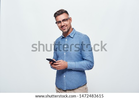 A nice chat. Portrait of handsome and cheerful bearded man in casual wear holding smart phone and looking at camera while standing against grey background