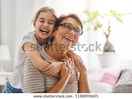 A nice girl and her grandmother enjoy sunny morning. Good time at home. Family playing in the bedroom.