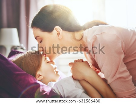 A nice girl and her mother enjoy sunny morning. Good time at home. Child sleeps. The mom wakes the kid with a kiss on the bed in the bedroom.