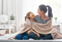 A nice girl and her mother enjoy sunny morning. Good time at home. Child wakes up from sleep. Family playing under blanket on the bed in the bedroom.