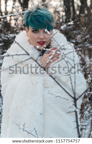 Stock Photo A nice girl with blue hair wrapped herself in a white fur coat in a snow-covered park. Rubbing against the background of a bush