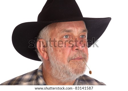 A nice image of a cowboy with a piece of straw in his mouth.