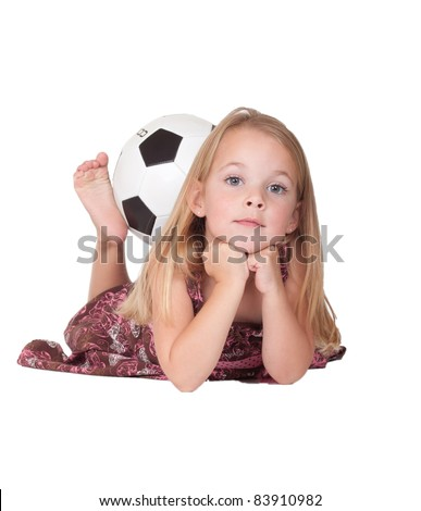 A nice image of a cute girl laying down with her soccer ball held by her feet. - stock photo