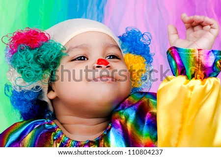 A nice kid wearing clown clothes and hair. The boy is very happy