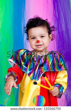 A nice kid wearing clown clothes. The boy is very happy on a colorful background. The toddler is on the floor with some toys.