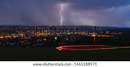 A nice long exposure photo from Reutlingen (Germany) on the Achalm (mountain) during a storm. The lightning hit the middle of the picture while the backlights of the car makses these lines.
