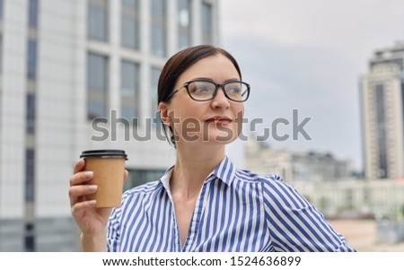 A nice looking busy girl stands against the backdrop of the city, holds a brown cup of coffe in her hand and looks away with smile. City view, business.