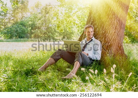 A nice looking grey hair man is sitting against a tree in the grass, looking at his computer. He is relaxing, enjoying the shadow of the tree in a sunny day. #256122694