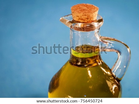 A nice looking little glass bottle with premium quality virgin olive oil closed with a cork. Oil jar close up isolated with blue background.