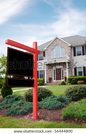 A nice luxury home with a blank for sale sign posted in front.  Plenty of copy space on the empty sign for your text.
