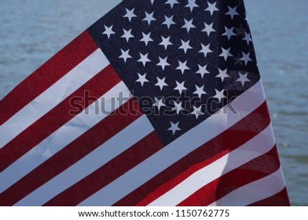 A nice United States flag with rich red and blue Stars and Stripes folded in the wind up close with a lake background.  Water from USA lake while patriots celebrate America on a summer day with symbol #1150762775
