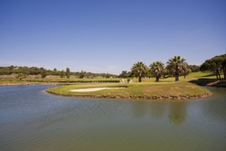 A nice view of a golf course with a lake and blue sky.
