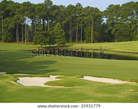A nice view of a pond and some sand traps on this Myrtle Beach golf course.