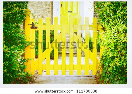 A nice yellow garden gate in front of an english house - stock photo