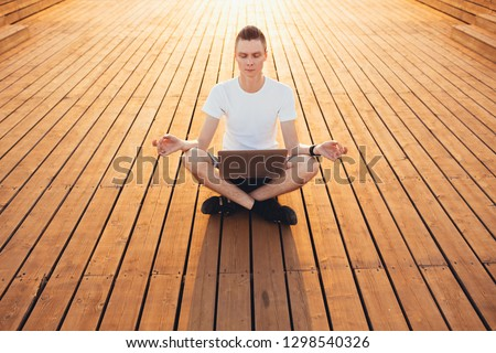 A nice young student guy is meditating while sitting on a wooden platform with a laptop. The concept of relaxation and self-knowledge. Learning and pursuing goals. Copyspace