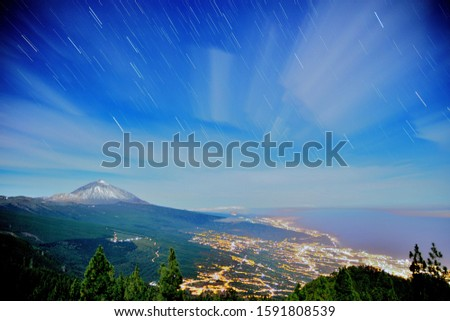 A night landscape of Teide mountain in Tenerife, Canary Islands, showing the lights of Puerto la Cruz and Orotava and the star trails and clouds trails