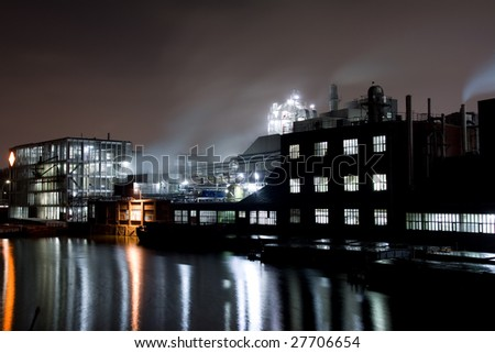 A night scene with a factory in an industrial area. There is a river and cargo ships in the front and the lights are reflected my the water.